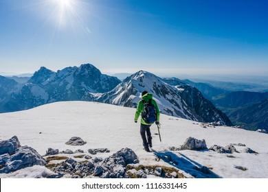A mountaineer walking on snow on a beautiful bright sunny day in the mountains. Adventure winter climb in alpine landscape. Alpinism in Kamnik Savinja alps, Slovenia.