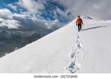 Mountaineer walking on the snowy slope of the Dovska Baba mountain in Karavanke range, Slovenia