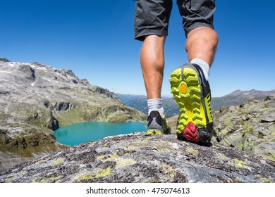 Mountaineer walking over a rock in the alps