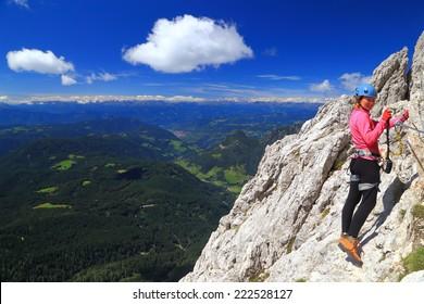 "Mountaineer woman climbs on via ferrata ""Passo Santner"", Catinaccio massif, Dolomite Alps, Italy"