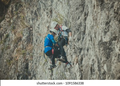 Mountaineer woman lifeguard (rescuer) in mountaineering equipment removes the victim from the cliff