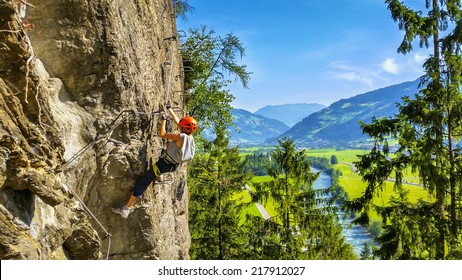 Mountaineer woman traverses on via ferrata, Zillertal Alps, Austria