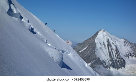 Mountaineering Rope Team on Steep Ridge on Dom with Weisshorn in the background, Switzerland