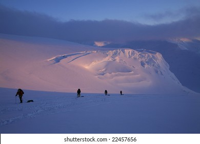 Mountaineering team ascending the upper Kahiltna Glacier to 11,200 camp, at around midnight, on Denali, Denali National Park, Alaska.
