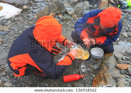 Mountaineers cooking during bad weather