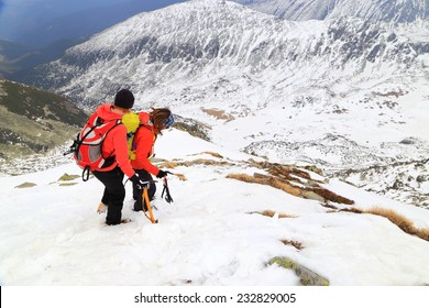Mountaineers descending a steep snow covered mountain with care