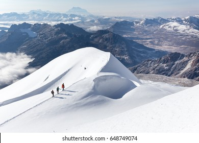 Mountaineers three climbers climbing mountain peaks ridge snow trail footpath  clouds, beautiful mountaineering tourism trekking Huayna Potosi mountain, Bolivia travel destination, sunrise morning .
