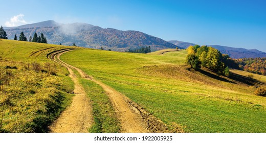 mountainous countryside in autumn. rural road through grassy pastures on hills rolling in to the distance. forest in colorful foliage. bright sunny day with bright blue sky