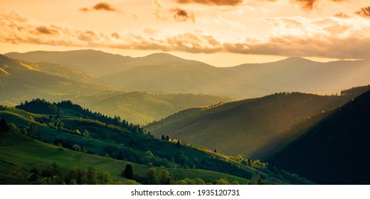 mountainous countryside scenery at sunset. dramatic sky above the distant valley. green fields and trees on the hill. beautiful nature scenery of carpathians