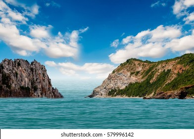 Mountainous island in the middle of the ocean on a beautiful blue sky.