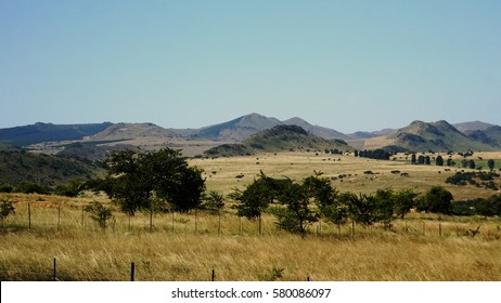 mountainous landscape in the Kingdom of Swaziland, hills and single trees, barren vegetation in autumn, cloudless sky/Mountainous landscape in Swaziland