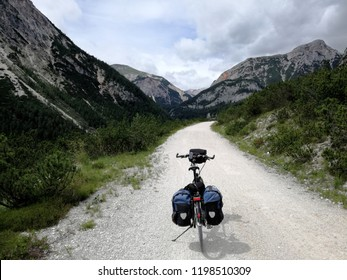 Mountainous - On a gravel path is a trekking bike with fully packed panniers waiting for the conquest of the mountains. It is cloudy and deserted.
