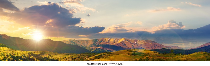 mountainous rural panorama landscape in springtime at sunset. beautiful scenery beneath a sky with clouds in evening light. grass covered hill rolling in to the distant ridge