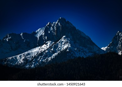 Mountainous snow and tree covered landscape.