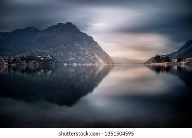 The mountains around Lecco reflected on the lake in a amazing cloudy day, Lombardy, Italy