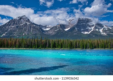 Mountains in the background and a beautiful blue river in the foreground.