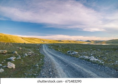 The mountains in beams of the evening sun. Mongolian Altai. Desert landscape, lake and mountains against the background of the colorful evening cloudy sky. Nature and travel. Mongolia