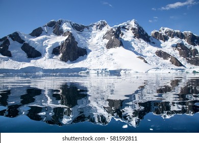 The mountains of Booth Island reflect in the water of Pleneau Bay, Antarctica