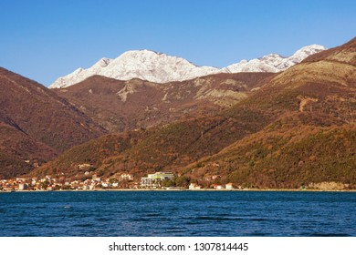 Mountains by the sea, winter Mediterranean landscape on sunny day. Montenegro, Adriatic Sea, Bay of Kotor. View of snow-capped mountain of Orjen,  Dinaric Alps