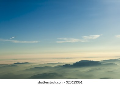 mountains clouds blue sky and fog photographed from on mountaintop
