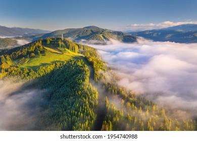 Berge in Wolken bei Sonnenaufgang im Sommer. Luftbild des Berggipfels mit grünen Bäumen im Nebel. Schöne Landschaft mit hohen Felsen, Wald, Himmel. Draufsicht von der Drohne des Bergtals bei niedrigen Wolken