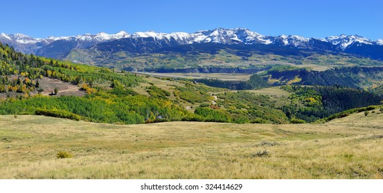 mountains with colorful yellow, green and red aspen during foliage season on Last Dollar road in Colorado