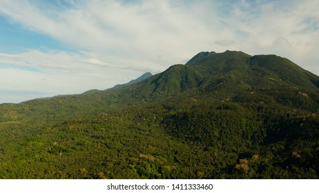 Mountains covered rainforest, trees and blue sky with clouds, aerial view. Camiguin, Philippines. Mountain landscape on tropical island with mountain peaks covered with forest. Slopes of mountains