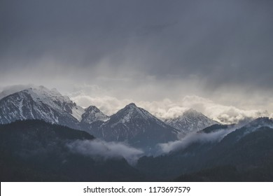 Mountains covered in snow with dark cloudy sky in rainy day
