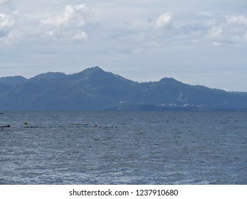 The mountains of Davao Oriental loom behind the waters of a beach in southern Philippines.