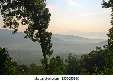 Mountains draped in low lying cloudy mist as seen from an overlook at daybreak
