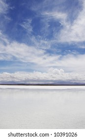 mountains with dynamic clouds in salt lake of uyuni bolivia on white beach with clear water