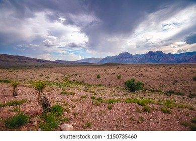 Mountains in the far off distance beyond an almost desolate desert landscape, blue sky peaking through shadowy storm clouds.