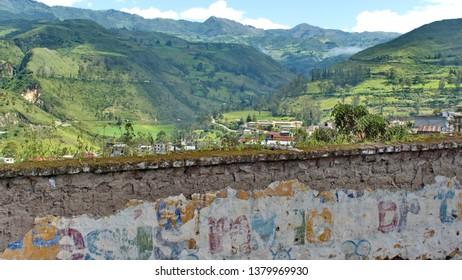 Mountains and farm land over the top of an old mud wall by the train station in Alausi, Ecuador
