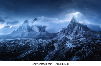 Mountains in fog at beautiful night. Dreamy landscape with mountain peaks, stones, grass, blue sky with blurred low clouds, stars and moon. Rocks at dusk. Tre Cime in Dolomites, Italy. Italian alps