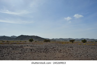 Mountains in gravel desert with blue sky, Oman