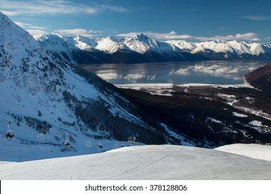 The mountains of the Kenai Peninsula reflect in the unusually calm waters of Turnagain Arm as skiers ride the lift to the top of the run at Alyeska Ski Resort in Girdwood, Aalska.