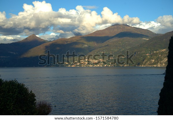 Mountains at the lake under a light cloudy blue sky