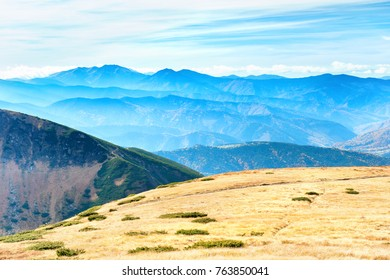 Mountains landscape with field of dry grass and blue sky