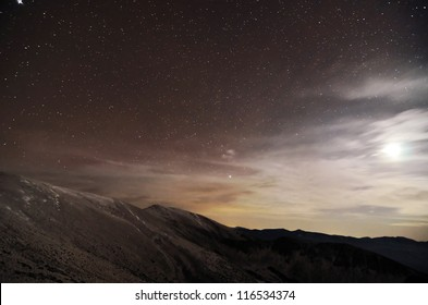 A mountains landscape at night with moonlight and stars