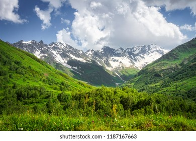 Mountains landscape. Rocky mountains with snowy peaks, green hills covered by grass in Alpine scene on bright sunny day with blue sky and clouds. Svaneti mountain landscape in Georgia. Amazing nature.