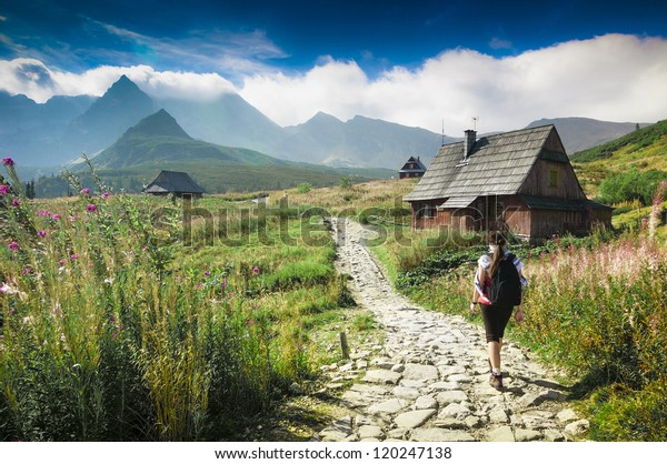 Mountains landscape. Young woman walking a trail in a green mountains. Hala Gasienicowa, Tatra Mountains, Poland.