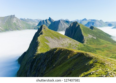 Mountains 'lille og store Brusen' coming up of the fog. Senja, Troms, Norway