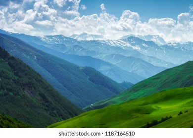 Mountains nature landscape on sunny summer day. Mountains ranges in Svaneti, Georgia. Scenery Hills and mountain. Amazing mountain range. Alpine. Green meadow covered by grass in highlands.