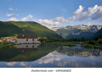 Mountains and nature of Prokletije National Park mirrored in the lake reservoir at old water mill in Gusinje. Mirror reflection photo