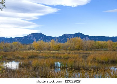 Mountains near Boulder, Colorado rise up above the nearby Walden Ponds wildlife refuge park