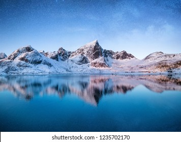 Mountains at the night time. Mountains and reflections on the water surface on Lofoten islands, Norway. Starry sky over the mountains. Winter landscape on Lofoten islands, Norway.