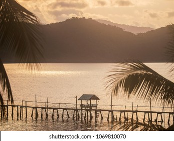 Mountains, palm trees and a wooden jetty over the ocean at dusk on Koh Chang island in eastern Thailand