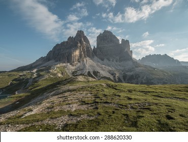Mountains Panorama of the Dolomites at Sunrise with clouds. Photograph is showing Tre Cime di Lavaredo in the Dolomites, Italy. Beautiful morning, just before the sunrise with soft tones and colors.