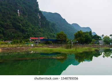 Mountains reflected in an ember green lake on the hidden Cat Ba Island which is regularly visited by boat tours around Ha Long Bay