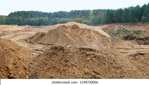 Mountains of sand in the forest at the construction site of new urban sewage systems. Panoramic collage from several autumn outdoor photos